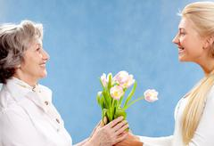 Portrait of young woman giving tulips to her mother Stock Photos