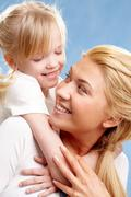 portrait of little daughter embracing her mother and looking at her - stock photo