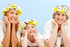 portrait of grandmother, mother, grandchild with diadems lying in the studio - stock photo