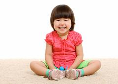 portrait of adorable girl with smiling sitting on the floor - stock photo