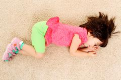 portrait of tired little girl sleeping on the floor after game - stock photo