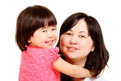 Portrait of mother and small daughter looking at camera Stock Photos
