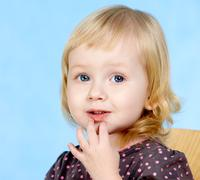 Stock Photo of portrait of adorable blonde girl isolated on blue background