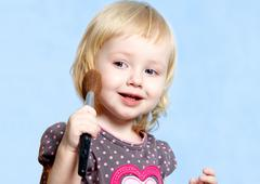 portrait of little blonde girl with brush - stock photo
