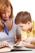 Portrait of woman and boy reading book together Stock Photos