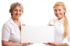 Portrait of mature lady and young woman holding paper Stock Photos