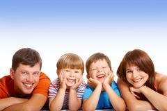 line of happy family members looking at camera and smiling over white background - stock photo
