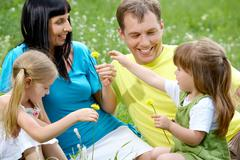 portrait of happy family spending time outdoors in summer - stock photo