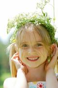 close-up of small cute girl wearing floral wreath looking at camera - stock photo