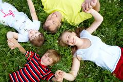 view from above of relaxing people lying on grass of meadow during rest - stock photo