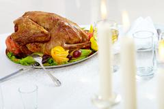 image of roasted turkey with flutes of wine and burning candles on christmas tab - stock photo