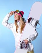 Portrait of healthy woman with pair of skis in hands looking somewhere Stock Photos