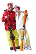 portrait of happy couple with skis in hands looking aside with smiles - stock photo