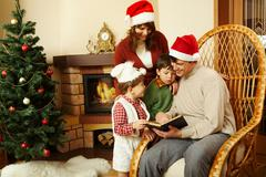 portrait of family gathered together to read interesting fairy tale with decorat - stock photo