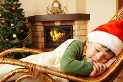 Photo of cute infant wearing santa cap sleeping in rocking chair under blanket Stock Photos