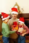 portrait of happy boys and their father holding giftboxes - stock photo