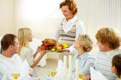 portrait of big family sitting at festive table and looking at aged female with - stock photo