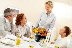 image of roasted turkey being cut by knife and fork on festive table portrait of - stock photo