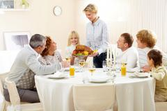 portrait of big family sitting at festive table and looking at pretty woman with - stock photo
