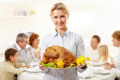 Portrait of pretty woman with roasted turkey on background of happy family Stock Photos