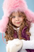 Happy girl in pink furry hat with snow in hands looking at camera Stock Photos