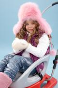 happy girl in furry hat with snow in hands sitting on sledge and looking at came - stock photo