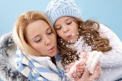 portrait of mother and her daughter blowing on snow in their hands - stock photo