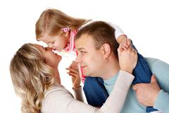 Stock Photo of portrait of happy parents and their daughter having fun in studio