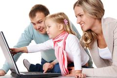 Friendly family looking at laptop monitor in studio Stock Photos