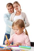 Photo of adorable girl drawing with highlighters with her parents behind Stock Photos
