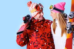 portrait of happy couple with skis in hands looking at each other and smiling - stock photo