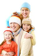 a family of four in winter clothes smiling and looking at camera - stock photo
