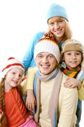 A happy family in winter clothing over white background Stock Photos