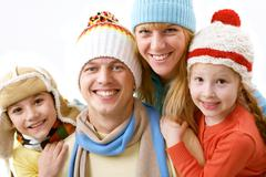 a portrait of a happy family of four in winter clothing - stock photo
