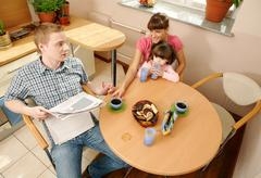 happy couple looking at each other during breakfast with their daughter near by - stock photo
