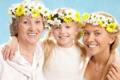 Portrait of grandmother with adult daughter and grandchild with floral diadems Stock Photos