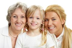 Faces of grandmother with adult daughter and grandchild in line Stock Photos