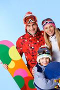 portrait of happy family with snowboards looking at camera on blue background - stock photo