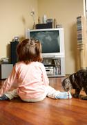 Rear view of little girl sitting on the floor and watching tv with cat near by Stock Photos