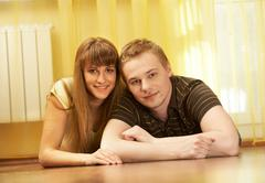 portrait of affectionate couple lying on the floor and looking at camera with sm - stock photo