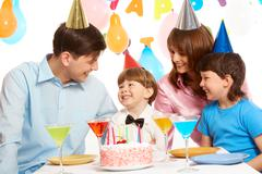 Portrait of happy boy having his birthday party with parents and elder brother n Stock Photos