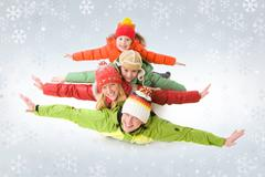 A family of four in warm clothing lying on each other with outstretched arms Stock Photos