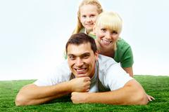 Portrait of happy family lying on grass and looking at camera Stock Photos