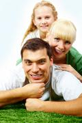 portrait of happy family lying on grass and looking at camera - stock photo
