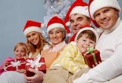 Portrait of happy family in santa caps with affectionate boy holding giftbox wit Stock Photos