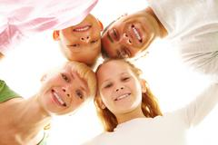 Below view of family members head by head smiling at camera Stock Photos