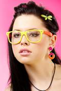 close-up of face pretty woman with glasses on a pink background - stock photo