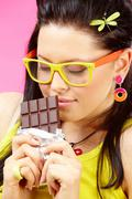 young woman enjoys and holds chocolate in bar - stock photo