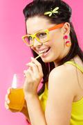 Portrait of beautiful woman drinking orange fizzy water Stock Photos