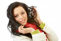 portrait of brunette wearing jacket touching her hair - stock photo
